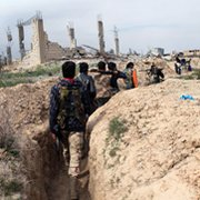 Syrian opposition fighters walk along a trench in the city of Deir Ezzor last week. Damascus on Tuesday asserted that rebels were plotting to conduct a chemical attack they would later blame on government forces.