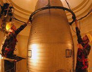 U.S. Air Force missile maintenance technicians attach a handling fixture to the reentry system of a Minuteman 3 missile inside a launch silo, during a June 2002 nuclear surety inspection at Malmstrom Air Force Base, Montana. Three House lawmakers are calling for Congress to use spending legislation again to deny the Pentagon any funds to begin decommissioning missile silos.