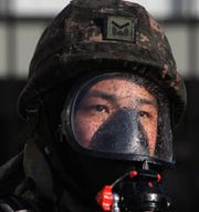 A South Korean soldier participates in a chemical weapons response drill in Seoul last November. A massive expansion of North Korea's premier chemical complex is likely to benefit the nation's chemical weapons production efforts, concludes a new expert analysis.