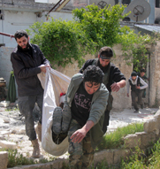 Syrian opposition fighters carry a comrade injured during clashes with government forces in Aleppo on Wednesday. Regime and opposition groups have exchanged new accusations of chemical-arms use in Syria's civil war.