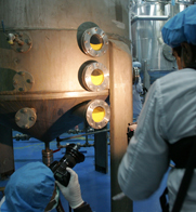 Photographers take pictures of machinery generating uranium hexafluoride in 2007 at Iran's Isfahan facility. Iran has diluted half of its 20 percent-enriched uranium, envoys said on Tuesday.