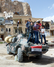 Children pose for a photograph on a Syrian army vehicle in the town of Maalula on Sunday. Governments are in disagreement about the future of an international mission to remove chemical weapons from Syria.