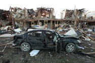 An apartment complex and a destroyed car lie in ruins next to a fertilizer plant that exploded on April 18, 2013, in West, Texas. Two of the 14 people that died in the blast lived at the apartment complex, the U.S. Chemical Safety Board said this week.
