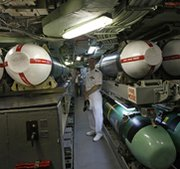 A U.S. Navy officer poses next to Tomahawk cruise missiles onboard the attack submarine USS Hampton. The Defense Department last week requested information on the potential development of a longer-range cruise missile.