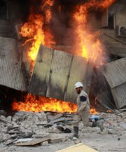 A Syrian emergency worker passes a burning building after a reported barrel-bomb attack in Aleppo last week. British officials on Thursday said President Bashar Assad's government has not declared its full stockpile of chemical-arms materials.