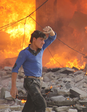 A man passes a burning building on Friday, after a reported government airstrike on the Syrian city of Aleppo. British, French and U.S. intelligence reportedly points to a strong possibility that President Bashar Assad's regime remains capable of deploying chemical weapons.