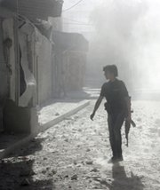 "A Syrian rebel fighter walks on a dust-covered street in Aleppo following a reported government airstrike on Sunday. The Organization for the Prohibition of Chemical Weapons on Tuesday said it would seek to ""establish facts"" about claims of chlorine-gas attacks in Syria."