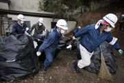 Japanese workers in March move radiation-contaminated leaves during a cleanup operation near the Fukushima Daiichi nuclear power plant in Japan. U.S. officials behind a controversial report on nuclear incident remediation reportedly backed by the White House have opted to extend the public comment period for the document by nearly two weeks (AP Photo/Greg Baker).