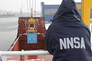 A U.S. National Nuclear Security Administration official watches as highly enriched uranium from the Czech Republic is loaded onto a ship in Poland for final transport to Russia. The semiautonomous Energy Department agency plans to cut funding for nonproliferation operations in the next budget (U.S. National Nuclear Security Administration photo).