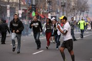 Racers and spectators flee after two explosions at the finish line of the Boston Marathon on Monday. President Obama pledged that the perpetrators would be brought to justice (AP Photo/The Daily Free Press).