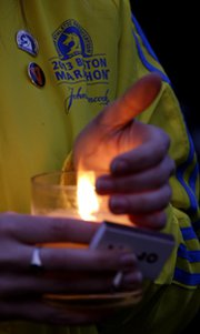 A Boston Marathon volunteer holds a candle during a Tuesday vigil for the victims of Monday's bombing (AP Photo/Julio Cortez).