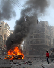 A Syrian passes near a burning vehicle after a reported government airstrike in Aleppo earlier this month. Syria's government has supplied a watchdog agency with additional information on its chemical-arms assets, according to officials.
