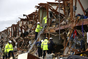 Firefighters last week search an apartment building that was devastated by the April 17 fertilizer plant explosion that killed at least 14 in West, Texas. Some are calling for tougher chemical security rules following the incident but it is unclear how Congress will act (AP Photo/LM Otero).