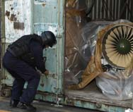 A police officer shows reporters a Russian-made jet engine removed last month from the North Korean-flagged freighter Chong Chon Gang. Panama Canal officials could assess as much as $1 million in penalties against Pyongyang for attempting to smuggle military gear through the waterway (AP Photo/Arnulfo Franco).