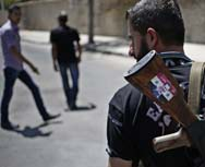 "A Syrian government soldier stands guard at a Damascus checkpoint on Wednesday, carrying an assault rifle with a sticker depicting Syrian President Bashar Assad and the Arabic-language words, ""Syria is fine."" Assad's regime denied opposition accusations that it had carried out a poison gas attack near the capital on Wednesday (AP Photo/Hassan Ammar)."