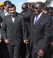 Zimbabwean President Robert Mugabe in 2010 welcomes then-Iranian President Mahmoud Ahmadinejad at Harare International Airport. A contested news report about a clandestine uranium trade understanding between Iran and Zimbabwe could revive debate over Tehran's ability to obtain uranium ore from other countries (AP Photo/Tsvangirayi Mukwazhi).