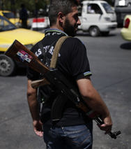 "A Syrian soldier's rifle features a sticker depicting Syrian President Bashar Assad's photograph and a ""Syria is fine"" slogan in Arabic. The White House joined other world governments in calling for a U.N. probe of allegations that Assad's regime unleashed a new and deadly chemical weapons attack, which Damascus denied (AP Photo/Hassan Ammar)."