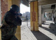 "A Syrian soldier takes aim at opposition fighters on Sunday near Damascus. There are worries that the Syrian government is ""cooking up recipes"" for chemical weapons, one U.S. official told CNN (AP Photo/SANA)."