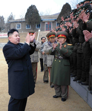 North Korean leader Kim Jong Un, at left, joins military personnel in applause during a January visit to a tank division. Pyongyang's announcement on Monday of a longer rocket launch window could mean the country's missile program is becoming more professionalized, one U.S. expert said (AP Photo/Korean Central News Agency).