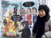 A South Korean woman on Sunday walks past a caricature of North Korean leader Kim Jong Un and his plans for another long-range rocket launch this month. Satellite images indicate the North is disassembling the rocket in order to fix a module glitch (AP Photo/Ahn Young-joon).