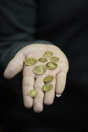 A goldsmith in Tehran holds Iranian gold coins in January. Six major powers are reportedly prepared to ease curbs on Iranian gold trade if the nation moves toward shuttering a uranium enrichment plant (AP Photo/Vahid Salemi).