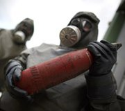 Workers in protective suits hold a dummy grenade during a demonstration at a chemical-weapons disposal facility in Germany. German- and Swedish-trained Libyan personnel helped destroy the last of their country's chemical arms in a secret operation that concluded last week.