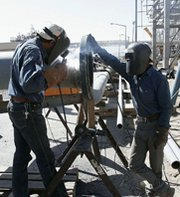 Metal workers weld together materials at Iran's Arak heavy-water reactor site in 2004. Tehran is open to modifying the facility to produce less plutonium, according to a senior Iranian nuclear official.