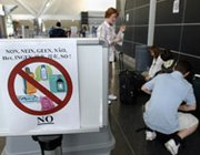 A group of travelers at JFK International Airport in New York in August 2006 repack their baggage to comply with new U.S. air travel regulations prohibiting liquids in carry-on luggage. The Transportation Security Administration this week temporarily renewed such a ban for direct U.S. flights to Russia, amid worries about terrorism threats to the Sochi Olympics.