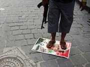 A Syrian rebel fighter stands on a picture of President Bashar al-Assad in Aleppo's Old Town in September 2012.