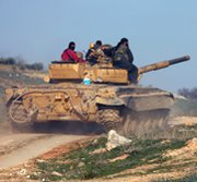 Syrian rebel fighters on Tuesday ride a tank toward the front line in a battle with Syrian government forces near the city of Hama. The United States is re-examining possible moves against the Syrian regime amid stalled diplomatic efforts.