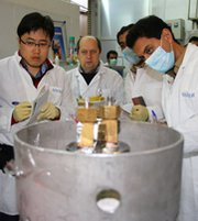 International Atomic Energy Agency inspectors and Iranian technicians on Jan. 20 disconnect centrifuge equipment used to enrich uranium to 20 percent purity at Iran's Natanz facility. Iran's stockpile of the weapon-useful substance has decreased in size under an atomic accord with world powers, the U.N. nuclear watchdog said on Thursday.