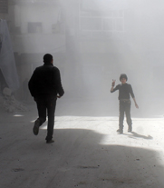 "A man runs down a street in the Syrian the city of Aleppo as a boy flashes a ""victory"" sign following an alleged Friday airstrike by the Syrian government. A U.N. official this week said security complications in the conflict-torn country are partly to blame for delays in the Syrian regime's transfer of chemical weapons into foreign custody."