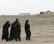 Women pass an anti-aircraft gun outside Iran's Natanz uranium-enrichment facility in 2006. Israel's intelligence minister on Sunday reaffirmed his country's right to take independent action to address Iran's disputed atomic efforts.