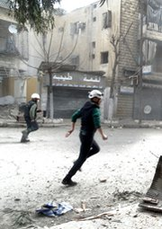 Rescuers run through dust following an alleged Syrian government airstrike on Wednesday in the city of Aleppo. The regime in Damascus reportedly has agreed to a plan calling for it to finish sending chemical-warfare materials to the Latakia seaport by late April.
