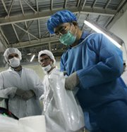 Technicians look on as an International Atomic Energy Agency inspector works at Iran's Isfahan uranium-conversion facility in 2005. The U.N. nuclear watchdog last year decided against issuing an assessment containing new information on the Middle Eastern nation's disputed nuclear program, according to insiders.
