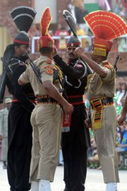 Pakistani Rangers, in black, and Indian Border Security Force personnel, in khaki, raise fists as part of a flag ceremony at the India-Pakistan Wagah Border Post last July. A senior Pakistani official this week said central authorities are to largely retain authority over the nation's nuclear arms in any future war against neighboring rival India.