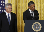 Former Senator Chuck Hagel, shown on Monday with President Obama, would have to deal with looming spending cuts at the Pentagon if selected to become the next U.S. Defense secretary (AP Photo/Carolyn Kaster).