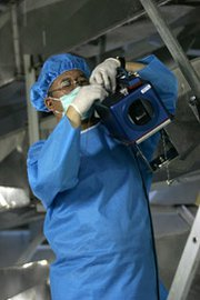 An International Atomic Energy Agency inspector installs a surveillance camera at Iran's Isfahan uranium conversion facility in 2005. The U.N. nuclear watchdog could assume an expanded role in a potential global nuclear-monitoring regime sought by authors of a new U.S. Defense Department advisory report.