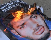 A poster of Yasin Bhatkal, an alleged founder of the Indian Mujahideen, burns after being set on fire by demonstrators celebrating his arrest in Bangalore on Aug. 29, 2013. Bhatkal is said to have sought access to a nuclear bomb for use against a city in western India.