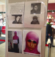 People visiting a department store in Sochi on Saturday walk past an information banner with the photos of suspected terrorists. Police are looking for a potential female suicide bomber believed to be at large in the Russian Black Sea resort town, which will be host to next month's Olympic games.
