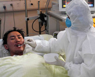 A nurse in 2009 feeds an avian influenza patient in China. U.S. National Institutes of Health on Friday said it would soon finalize a policy on federal funding of studies that aim to produce more contagious or virulent versions of H5N1 to prepare against more dangerous strains of the virus occurring in nature (AP Photo/Xinhua News Agency).