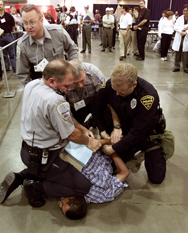 Police officers practice subduing an individual playing the part of an anthrax victim as part of a bioterrorism drill in Tuscon, Ariz., in 2002. The U.S. Health and Human Services Department is awarding $840 million in new grants to benefit state and local emergency-response programs.