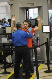 An air traveler is patted down after passing through a full-body scanner at a security checkpoint at Los Angeles International Airport in February. The U.S. government has ordered tightened screening measures at a number of foreign airports with U.S.-bound flights following new intelligence that al-Qaida has developed a new bomb that can fool airport security.