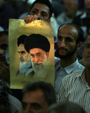 A man in Tehran last month holds an image of Iranian supreme leader Ayatollah Ali Khamenei and his late predecessor. Khamenei on Tuesday said his country plans to eventually pursue a nearly 20-fold increase to its uranium-enrichment capacity.