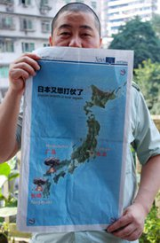 A man shows a full-page map that ran in a local Chinese newspaper last week depicting apparent atomic bomb clouds above Japan. Tokyo on Wednesday strongly condemned the publication.