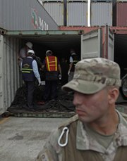 A police officer stands guard on Wednesday as investigators examine military equipment found aboard the North Korean-flagged freighter Chong Chon Gang in Panama. Pyongyang on Thursday demanded an immediate release of the vessel and its crew (AP Photo/Arnulfo Franco).