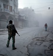 A Syrian rebel fighter stands on a street in Aleppo following a reported government airstrike on Monday. British legislators criticized their government over 2012 exports of potential chemical-arms ingredients to Syria.