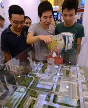 Students look at a model of a Russian nuclear power plant on display at an international nuclear power exhibition held in Hanoi in 2012. A U.S. Senate committee on Tuesday endorsed a new U.S. accord to cooperate with Vietnam on its atomic energy program, but moved to limit it and most future pacts to 30-year duration.