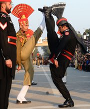 "Pakistani Rangers, seen in black uniform, and Indian Border Security Force personnel, in khaki, perform the ""flag off"" ceremony at the Pakistan-India Wagah border post in January 2013. Pakistani Prime Minister Nawaz Sharif is said interested in reducing nuclear-arms tensions between the two nations in upcoming peace talks."