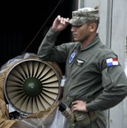 A naval police officer stands on Tuesday near a Russian-made jet engine taken from the North Korean-flagged freighter Chong Chon Gang. The ship seized in Panama earlier this month reportedly contained five vehicles that might include missile control features (AP Photo/Arnulfo Franco).